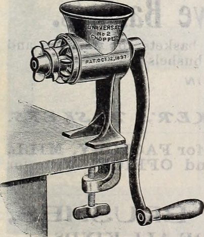Manual meat grinder attached to a wooden counter-top